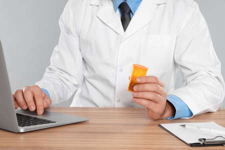 Professional pharmacist working with laptop at table against light grey background, closeup
