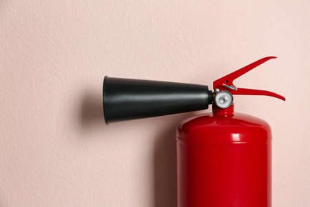 Fire extinguisher on pink background, closeup view