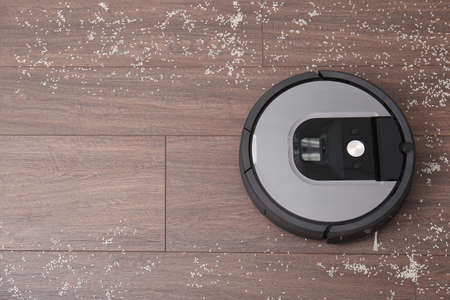 Removing groats from wooden floor with robotic vacuum cleaner at home, top view. Space for text 스톡 콘텐츠