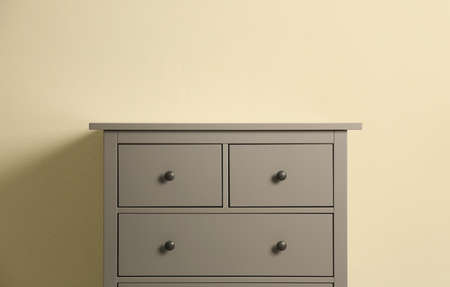 Grey chest of drawers on beige background