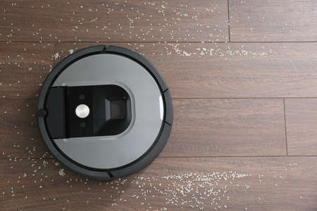 Modern robotic vacuum cleaner removing scattered rice from wooden floor, top view. Space for text