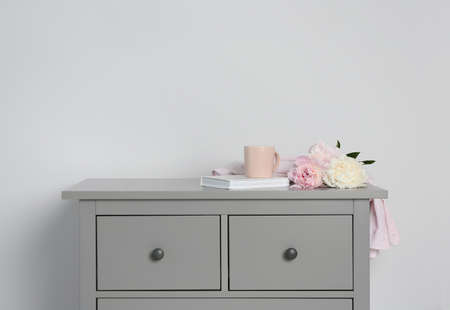 Grey chest of drawers on light background Stockfoto