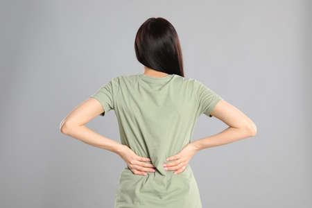 Woman suffering from lower back pain on light grey background. Visiting orthopedist