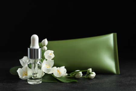 Cosmetic products and flowers on grey stone table against black background