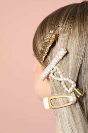 Young woman with beautiful different hair clips on pink background, closeup
