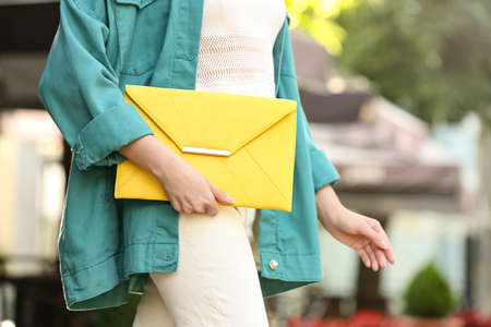 Young woman with elegant envelope bag outdoors on summer day, closeup