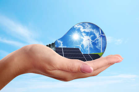 Alternative energy source. Woman holding light bulb with solar panels and wind turbines, closeup Banque d'images