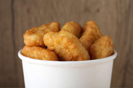 Bucket with tasty chicken nuggets on wooden background, closeup