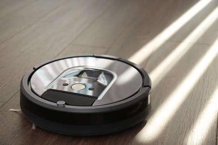 Modern robotic vacuum cleaner on wooden floor