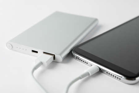 Smartphone charging with power bank on white background, closeup