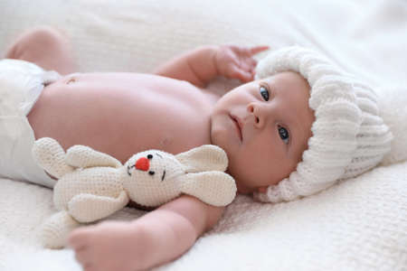 Cute newborn baby with toy in white knitted hat on plaid Stock fotó