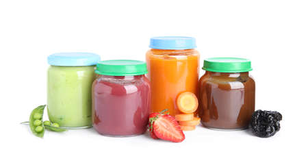 Jars with baby food and fresh ingredients on white background
