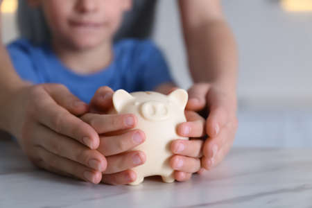 Mother and son with piggy bank at marble table indoors, closeup