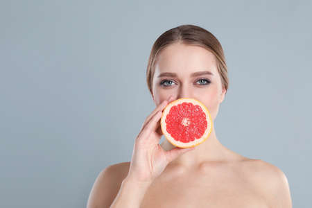 Young woman with cut grapefruit on grey background. Vitamin rich food