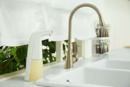 Modern automatic soap dispenser near sink in kitchen