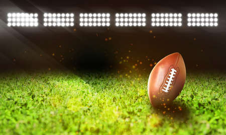 Leather American ball on green football field, space for text  Banque d'images