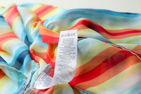 Clothing label with care instructions on colorful striped garment, closeup