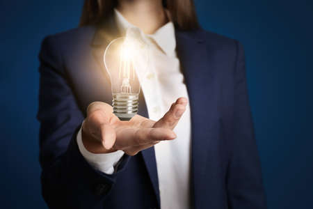 Idea concept. Businesswoman with glowing light bulb on dark background, closeup Banque d'images - 150658602