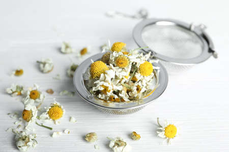 Dry chamomile flowers in infuser on white wooden table, closeup
