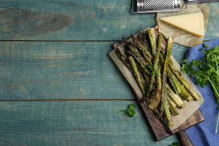 Oven baked asparagus served with lemon and parsley on blue wooden table, flat lay. Space for text