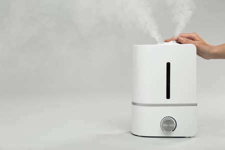 Woman using modern air humidifier on light grey background, closeup. Space for text Фото со стока