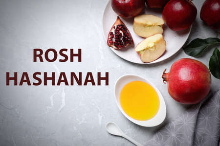 Honey, apples and pomegranate on marble table, flat lay. Rosh Hashanah holiday