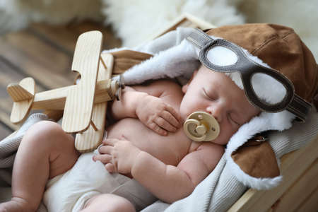 Cute newborn baby wearing aviator hat with toy sleeping in wooden crate