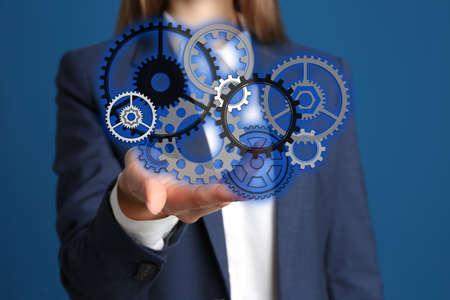 Businesswoman demonstrating gear mechanism on blue background, closeup