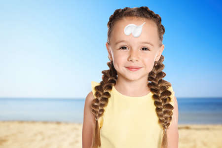 Adorable little girl with sun protection cream on face at sandy beach