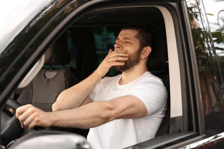 Tired man yawning while driving his modern car 免版税图像