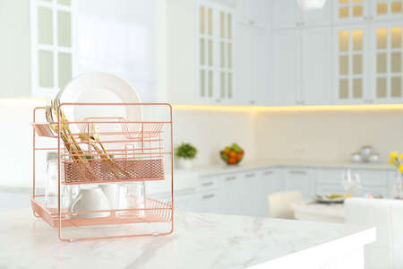 Clean dishes on drying rack in modern kitchen interior, space for text