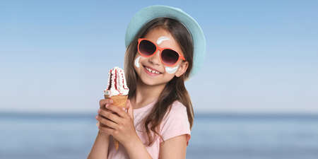 Adorable little girl with sun protection cream on face at beach, banner design