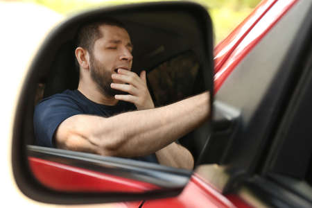 Tired man yawning in his auto, view through car side mirror