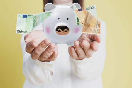Young woman holding piggy bank and Euro banknotes falling on color background, closeup