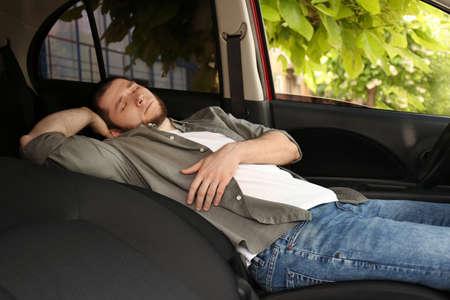 Tired man sleeping in his modern car