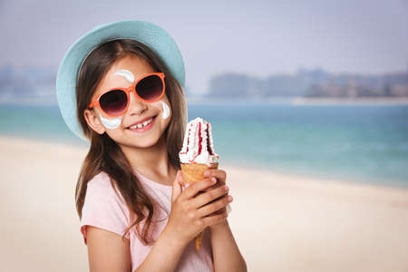 Adorable little girl with sun protection cream on face at sandy beach, space for text