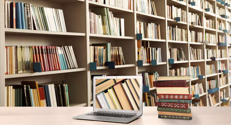 Digital library concept. Modern laptop on table and shelves with books indoors