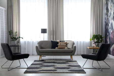 Modern living room interior with comfortable sofa and armchairs