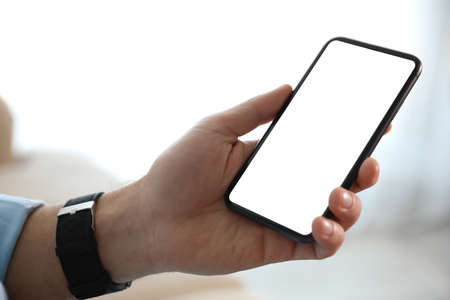 Man holding mobile phone with empty screen indoors, closeup Foto de archivo