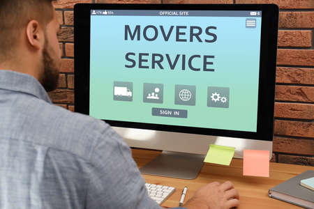 Young man using computer to order movers service in office, closeup Standard-Bild