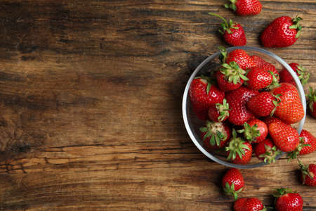 Delicious ripe strawberries in glass bowl on wooden table, flat lay. Space for text