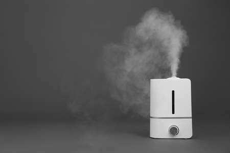 Modern air humidifier on grey background. Space for text Фото со стока