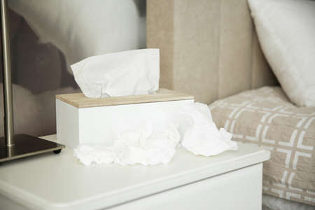 Used paper tissues and holder on table in bedroom