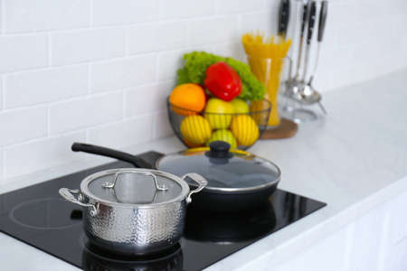 Saucepot and frying pan on induction stove in kitchen Stock Photo