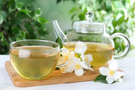 Tasty tea and fresh jasmine flowers on white wooden table