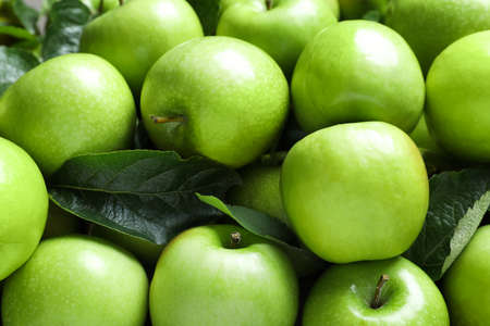 Pile of tasty green apples with leaves as background, closeup