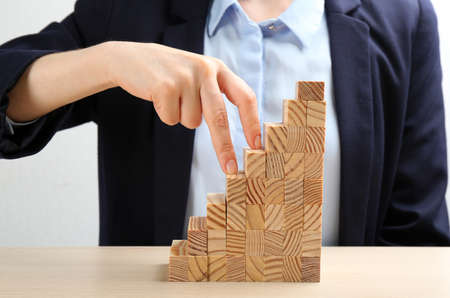 Woman imitating stepping up on wooden stairs with her fingers at table, closeup. Career promotion  concept