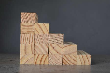 Steps made with wooden blocks on table against grey background. Career ladder Zdjęcie Seryjne
