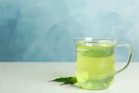Cup of aromatic green tea and leaves on light wooden table. Space for text