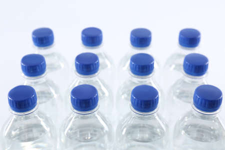 Plastic bottles with pure water on white background, closeup